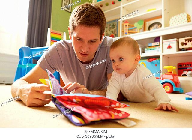 Mid adult man and baby daughter reading storybook in playroom