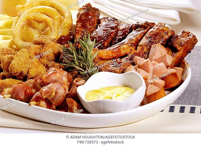 Meat platter with mustard sauce, riblets, sausages, crumbed chicken, onion rings and chips, food