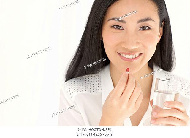 Mid adult woman taking tablet, portrait