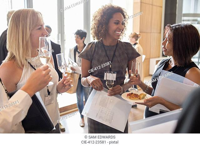 Businesswomen holding flutes of champagne and documents during meeting break