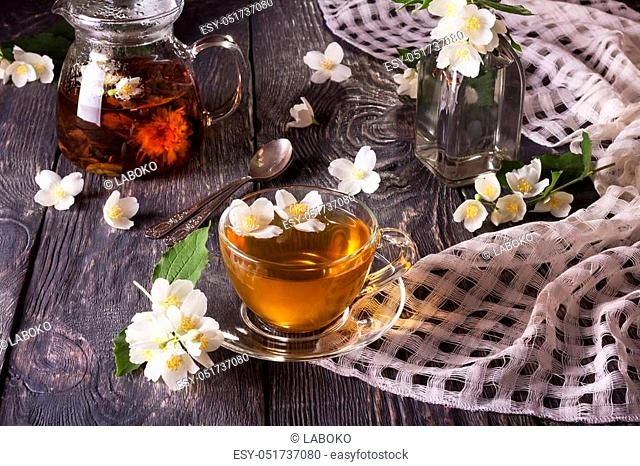 Herbal tea in teapot and Cup, Jasmine flowers scattered on gray wooden table