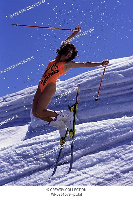 woman wearing a swimsuit doing acrobatics on her skies in the Alps