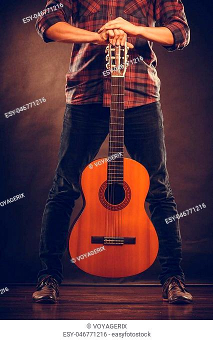 Music, hobby concept. Guitarist is standing with wooden guitar. Man is holding the instrument