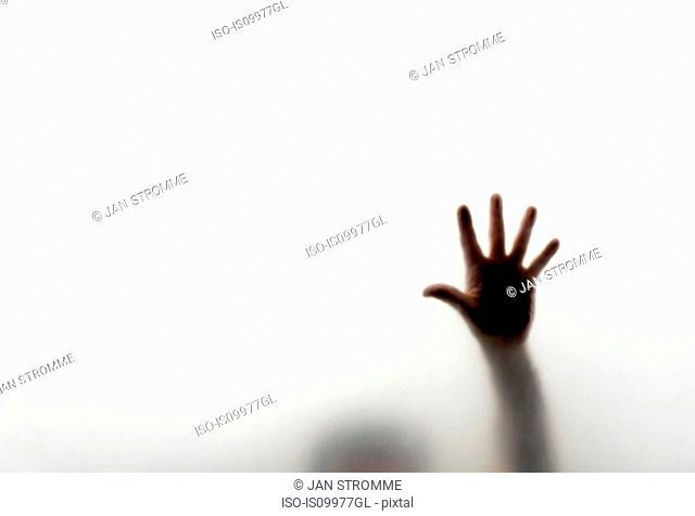 Man pressing hand against window