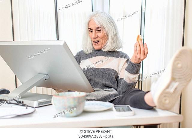 Portrait of senior woman sitting at computer with foot on desk