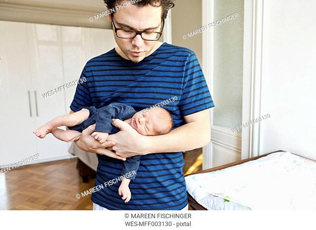 Father holding newborn son at home