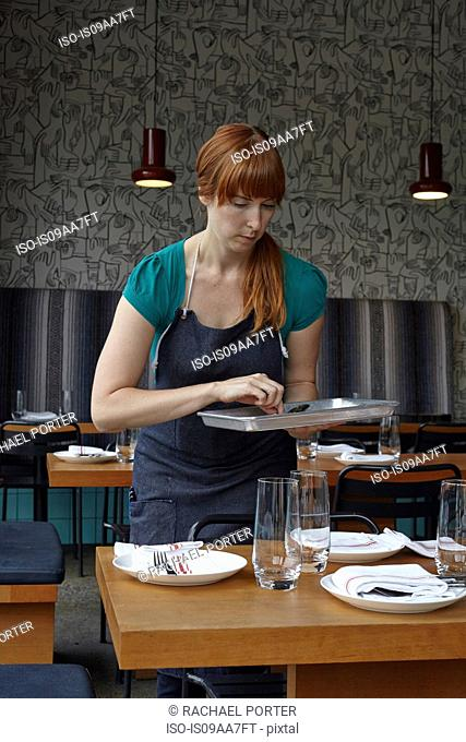 Mid adult woman preparing table in restaurant