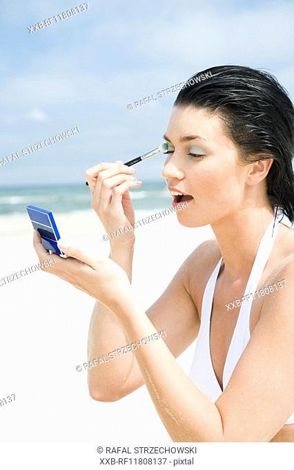 woman doing makeup on beach
