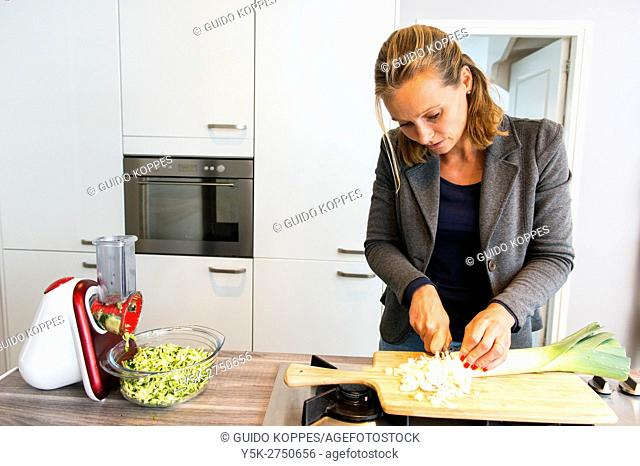 Kaatsheuvel, Netherlands. Mid adult woman cutting up groceries in preparation for a lasagna dish