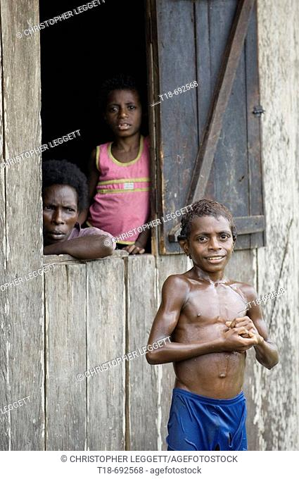 Boy smiling with mother watching from window, Indonesia