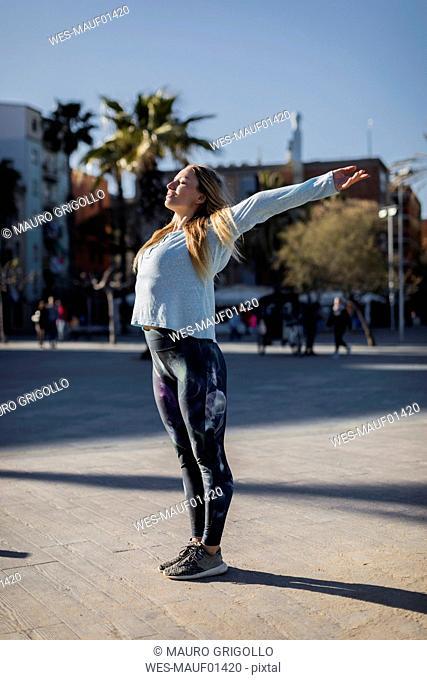 Spain, Barcelona, woman stretching on beach promenade