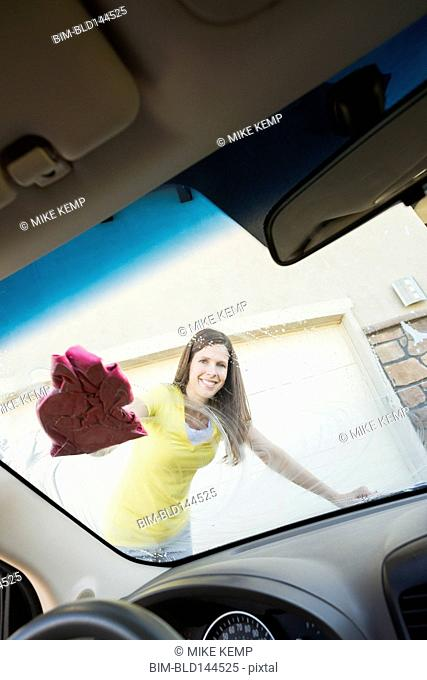 Caucasian woman washing car windshield