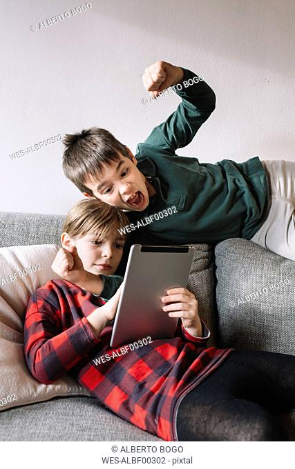 Girl lying on the couch in the living room using tablet while her brother interrupting