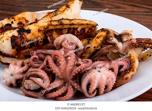 Boiled octopus with squid in the bowl on wooden background