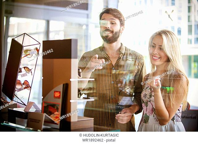 Young couple looking through shop window