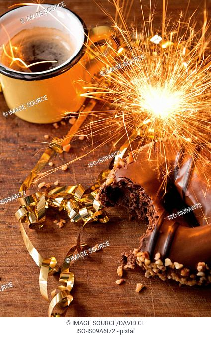 Sparkler, doughnut and cup of coffee