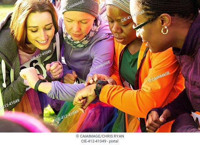 Female runners checking smart watches at charity run