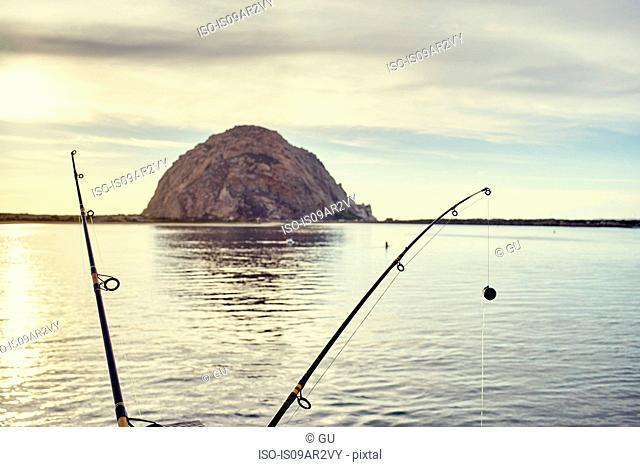 View of Morro Bay Rock between fishing rods, Morro Bay, California, USA