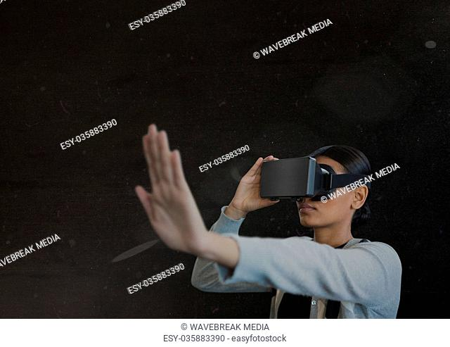 young woman using vr headset in the dark