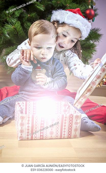 Little brothers opening their presents close to Christmas tree. They are illuminated by magical light from gift box
