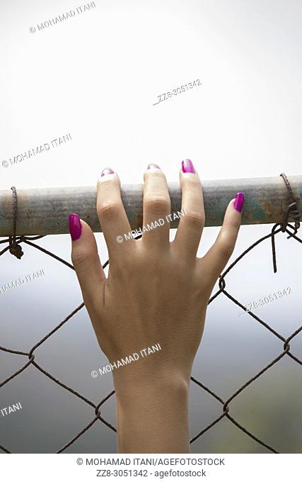 Close up of a woman's hand on metal fence