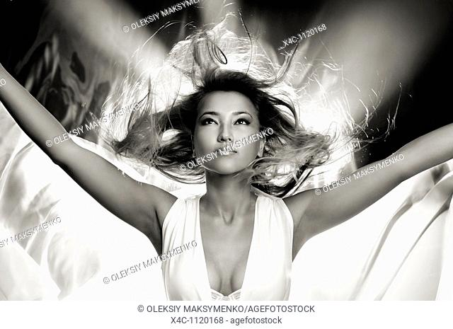 Beautiful young godlike woman with her hair flying in the wind