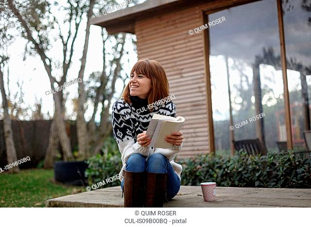 Woman sitting on picnic table holding book looking away smiling