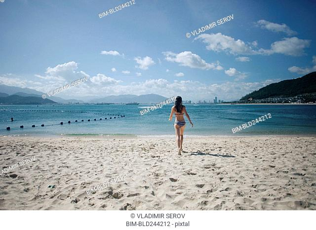 Caucasian woman wearing bikini running on beach