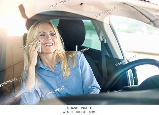 Smiling woman in car on cell phone