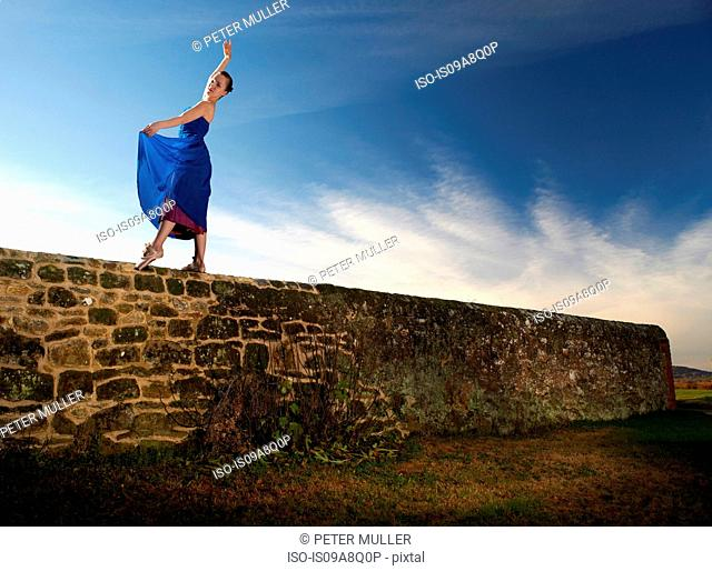 Female dancer poised on stone wall
