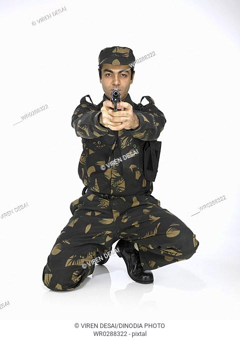 Indian army soldier sitting on knee pointing handgun MR702A