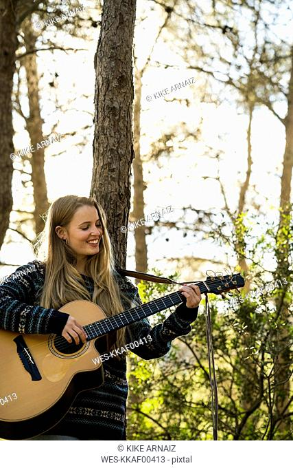 Happy young woman playing guitar in nature