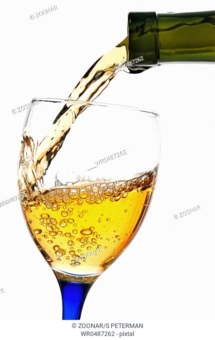 White wine flowing from a green bottle to a glass. All is isolated with a clipping path