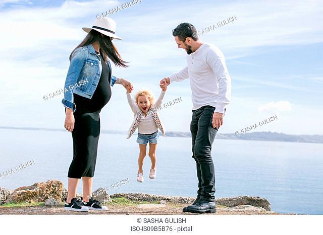 Pregnant mature couple swinging daughter at coast