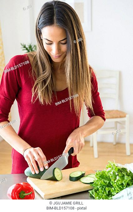 Caucasian woman slicing vegetables for salad