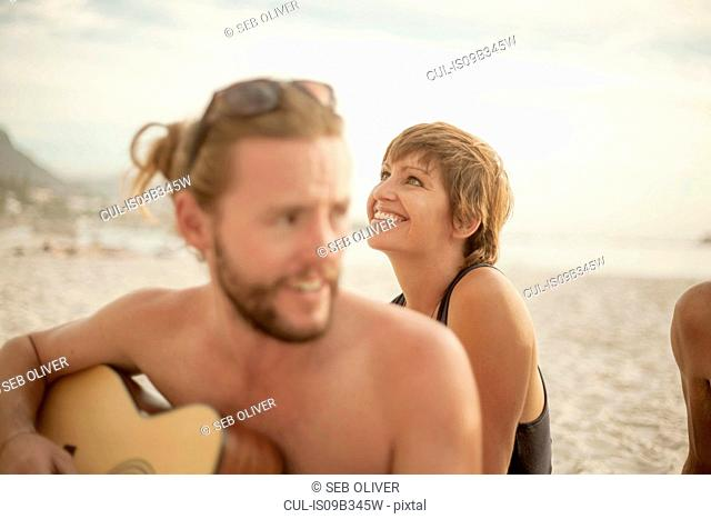 Group of friends sitting on beach, man playing guitar