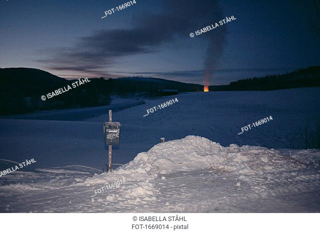 Mail box on snow covered landscape with campfire in background at dusk, Jarvso, Sweden