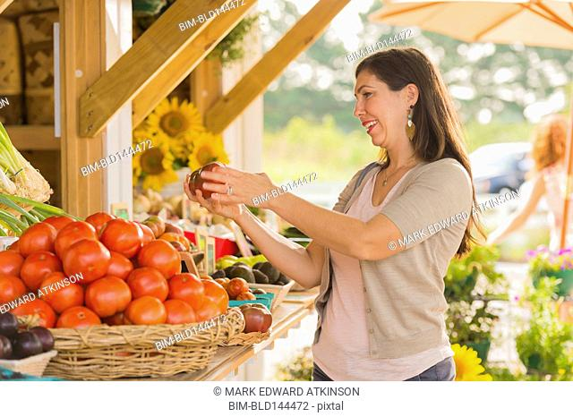 Hispanic woman browsing fruit at farmers market