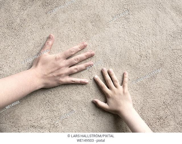 Two hands connecting. Adult and child hand meet, touching a wall. Conceptual image of connection between parent and kid, childhood and togetherness