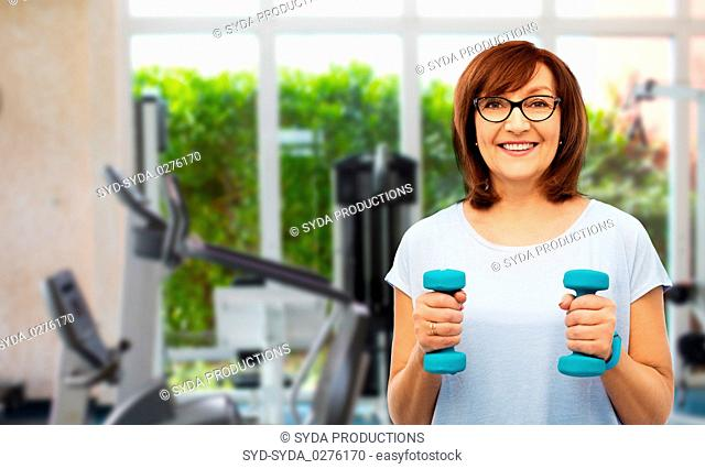 senior woman with dumbbells exercising in gym