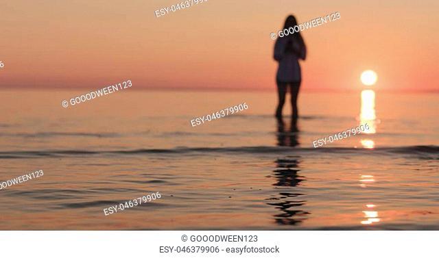 closeup teenage girl walking in shallow water on a beach, wide photo