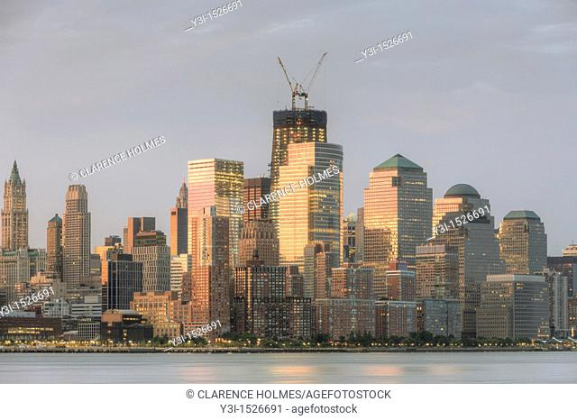 The sunrise colored sky is reflected off of the building facades in lower Manhattan, including the World Financial Center and Battery Park City in New York City