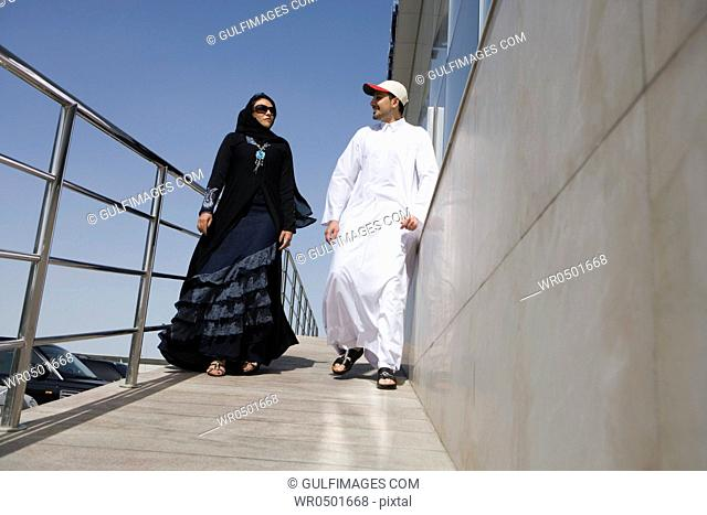 Young couple walking by railing