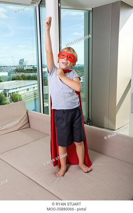 Boy in super hero costume standing with arm raised on sofa bed at home