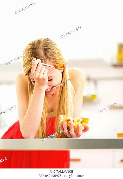 Laughing young woman eating fresh fruits salad in kitchen