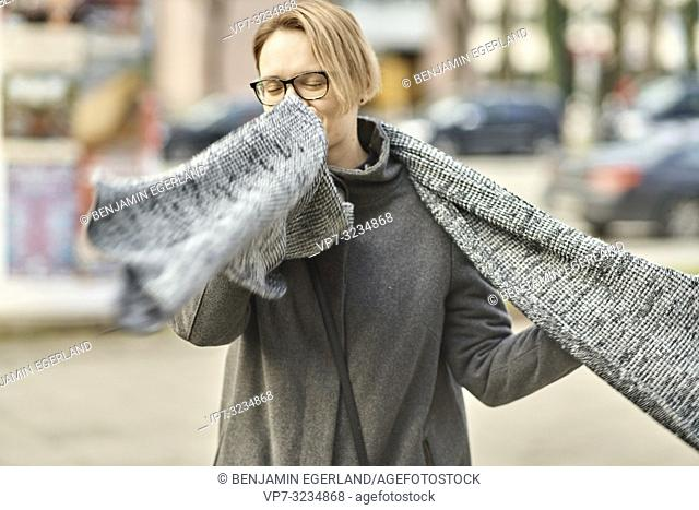 woman playing with scarf at street in city Munich, Germany. Women's winter clothing