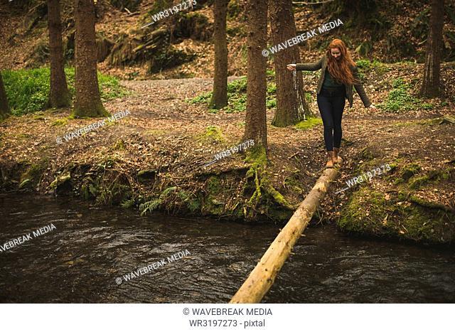 Female hiker walking on the fallen tree trunk across the river