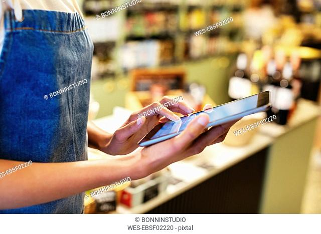 Close-up of woman using tablet in a store