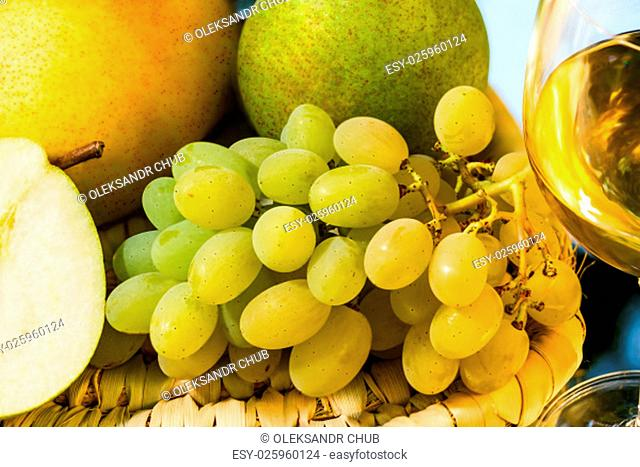 ripe juicy appetizing grape, pears and glass of wine on mirror background