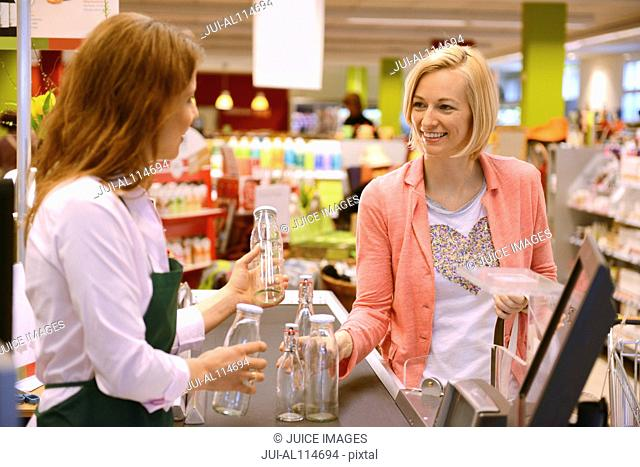 Customer returning glass bottles at the checkout of organic grocery store